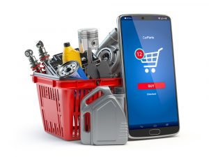 Car parts, spares and accesoires in shopping basket and smartphone isolated in white. Online purchasing and delivery of car spare concept.